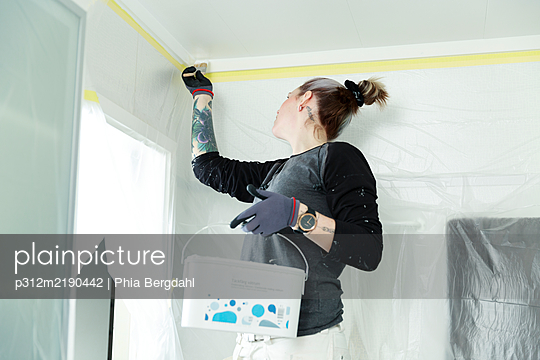 Woman painting ceiling - p312m2190442 by Phia Bergdahl