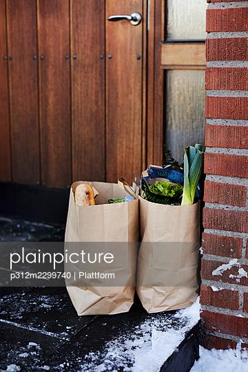 Groceries in paper bags in front of house door - p312m2299740 by Plattform