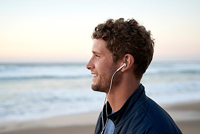 Man on beach using earphones - p1124m1510946 by Willing-Holtz