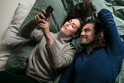 High angle view of smiling couple taking selfie through smart phone while lying on bed - p426m1570260 by Maskot