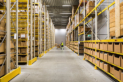 Mid distance view of senior male warehouse worker pushing cart on aisle in industrial building - p426m2018840 by Maskot