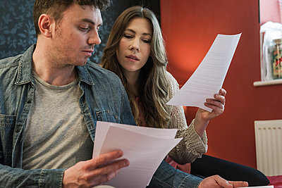 Couple looking at paperwork - p429m1027865f by Colin Hawkins