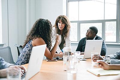 Business people using laptop in meeting - p555m1504106 by John Fedele