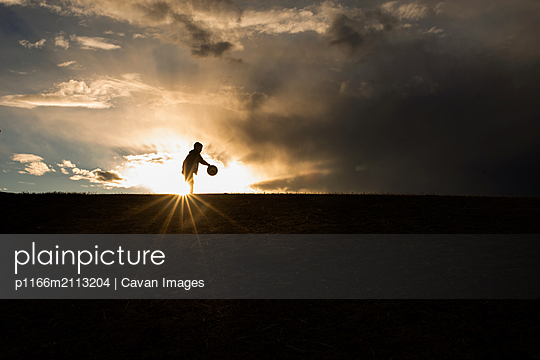 Silhouette of 5 year old boy playing basketball - p1166m2113204 by Cavan Images