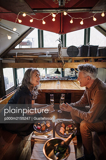 Senior couple having a candlelight dinner on a boat in boathouse - p300m2155247 by Gustafsson