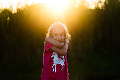 Portrait of happy girl hugging self during sunset - p1166m1486207 by Cavan Images