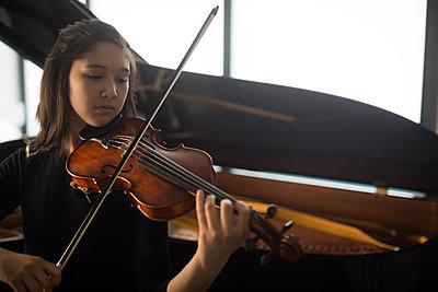Adorable schoolgirl playing violin in music school - p1315m2003037 by Wavebreak