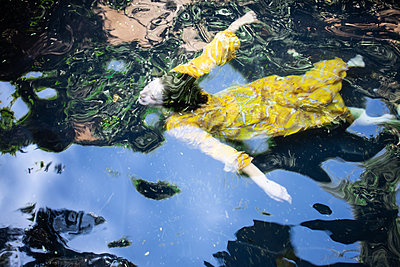 Woman in yellow dress swimming in lake - p1640m2259933 by Holly & John
