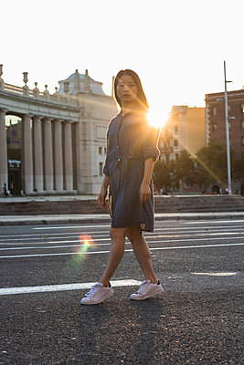 Woman walking on street in city against clear sky during sunset - p300m2243966 by NOVELLIMAGE