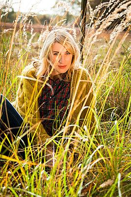 Frau sitzt zwischen Gräsern auf der Wiese - p904m740448 von Stefanie Päffgen
