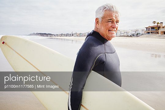 Smiling senior man standing on a beach, wearing a wetsuit and carrying a surfboard. - p1100m1177585 by Mint Images