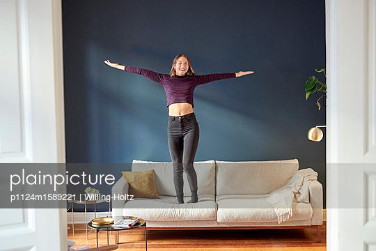 Junge Frau tanzt auf dem Sofa - p1124m1589221 von Willing-Holtz