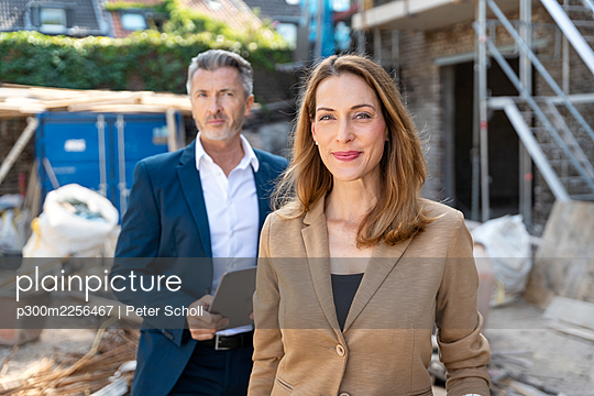 Businesswoman smiling while standing with colleague at construction site - p300m2256467 by Peter Scholl