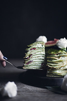 Cropped image of woman removing slice of pancake - p1166m1231676 by Cavan Images