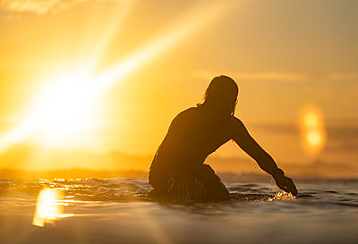 Surfing the sunrise in Costa Rica - p1166m2153332 by Cavan Images
