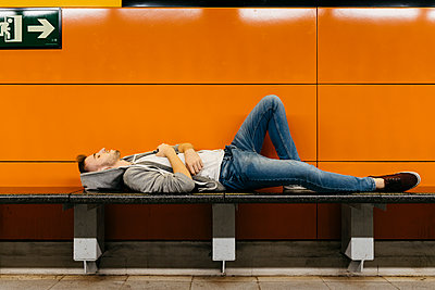 Young man waiting for the metro, resting on bench - p300m2059015 by Josep Rovirosa