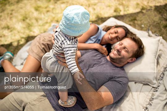 Familie mit Baby entspannt sich am Seeufer - p1355m1574055 von Tomasrodriguez