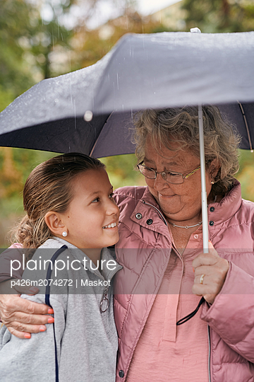 Grandmother embracing granddaughter while sharing umbrella with her in park during rainy season - p426m2074272 by Maskot
