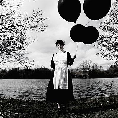 Dienstmädchen hält schwarze Luftballons - p1521m2158315 von Charlotte Zobel