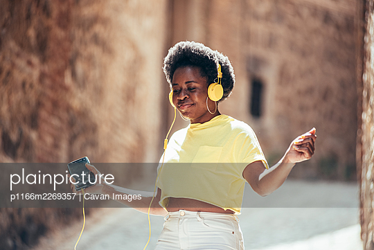 Portrait of a black girl with afro hair listening to music and dancing in an old city street. - p1166m2269357 by Cavan Images