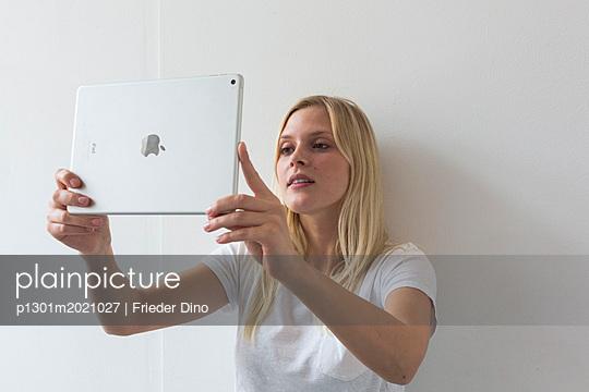 Junge, blonde, moderne Frau während einer Besprechung mit Ipad - p1301m2021027 von Delia Baum