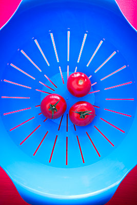 Top view of three tomatoes in a blue strainer - p1166m2107813 by Cavan Images