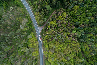 Aerial view of rural road through forest, Franconia, Bavaria, Germany - p300m2121866 by Martin Rügner