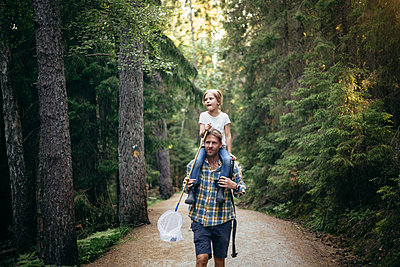 Father carrying daughter on shoulder while walking in forest - p426m2213251 by Maskot