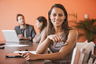 Mixed race businesswoman smiling at meeting table - p555m1463676 by John Fedele