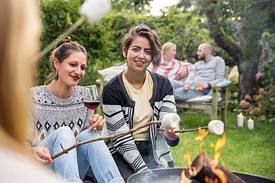 Friends roasting marshmallows - p788m1165409 by Lisa Krechting