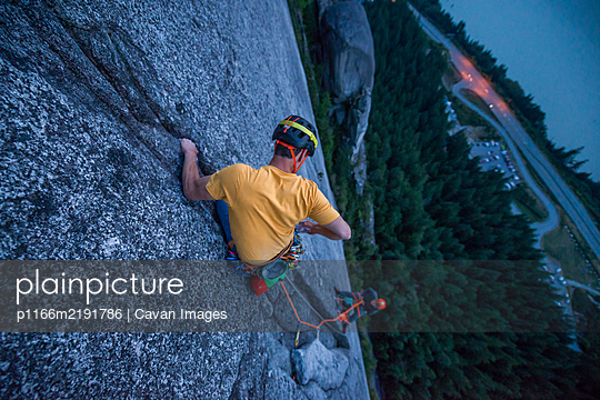 Top view man rock climbing at sunset above the sea and highway - p1166m2191786 by Cavan Images
