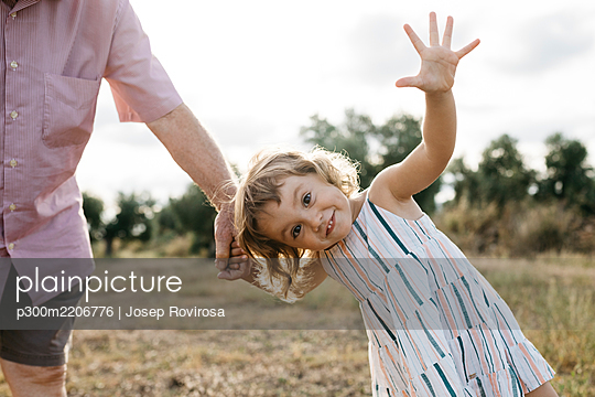 Cheerful cute girl holding grandfather's hand while standing on land against sky - p300m2206776 by Josep Rovirosa