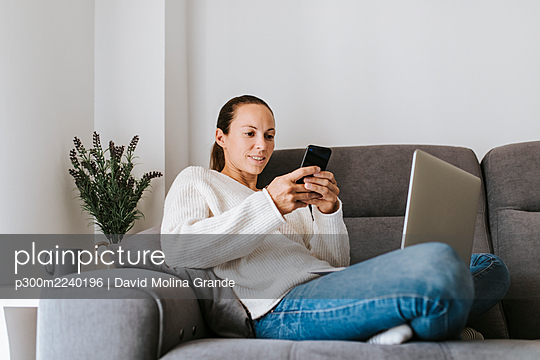 Woman text messaging through smart phone while sitting with laptop on sofa - p300m2240196 by David Molina Grande