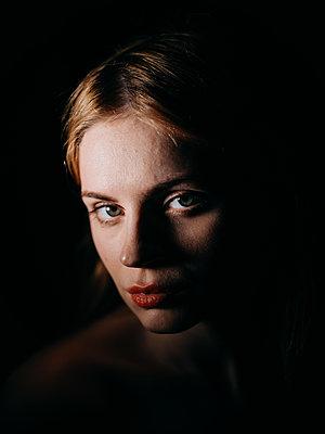 Junge Frau vor schwarzem Hintergrund - p1184m1440818 von brabanski