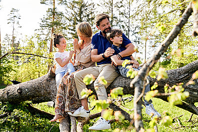 Family sitting on fallen tree in forest - p300m2197539 by Stefanie Aumiller