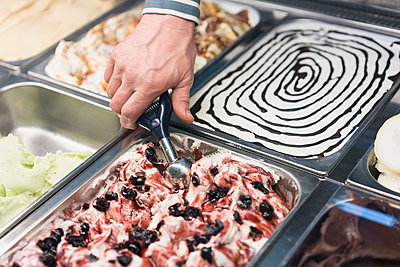 Detail of hand scooping ice cream from container at store - p301m1180536 by Halfdark