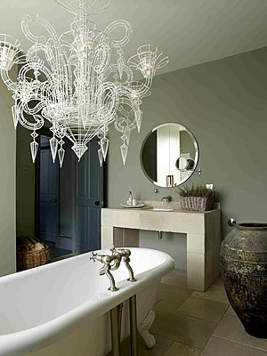 Atelier wirework Neo-Baroque chandelier hanging above roll top bath in neutral grey and stone tiled bathroom - p349m790615 by Polly Eltes