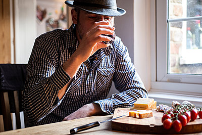 Man drinking wine and eating mediterranean food in cafe - p429m2097516 by Bonfanti Diego
