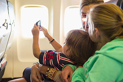 Caucasian family sitting on airplane - p555m1522880 by Marc Romanelli