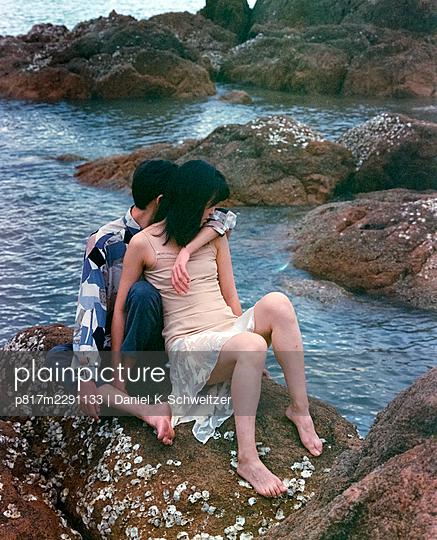 Love couple sitting on rocky coast - p817m2291133 by Daniel K Schweitzer