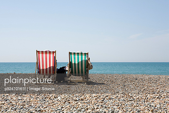 People in deckchairs at the beach - p92410161f by Image Source