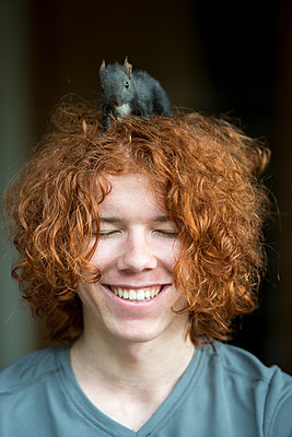 Portrait of happy redheaded teenage boy with squirrel on his head - p300m1469663 by Lisa und Wilfried Bahnmüller