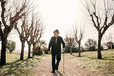 Spain, Barcelona. Retired senior man walking through a park in winter with his cane - p300m2167179 von Josep Rovirosa