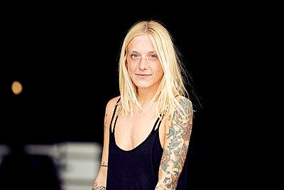 Smiling young woman standing at parking garage - p300m2268163 by Uta Konopka