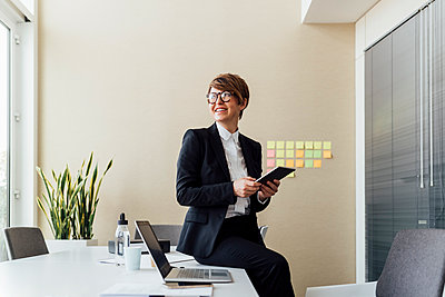 Thoughtful businesswoman holding digital tablet while sitting on desk in office - p300m2275697 by Eugenio Marongiu