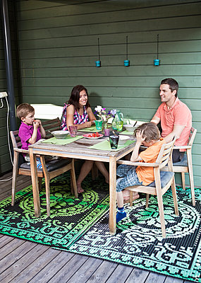 Happy family having breakfast together at porch - p426m1093318f by Maskot