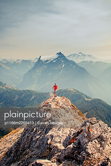 Hiker wearing red shirt stands on mountain top with scenic view behind - p1166m2269413 by Cavan Images