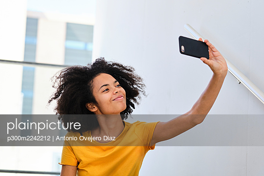 Smiling student taking selfie through mobile phone while sitting at university - p300m2242212 by Antonio Ovejero Diaz