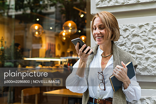 Smiling woman using mobile phone while standing in front of wall - p300m2286800 by NOVELLIMAGE