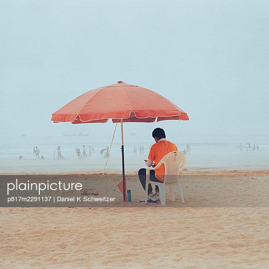 Man sitting under a parasol on the beach - p817m2291137 by Daniel K Schweitzer